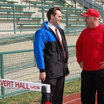 two men having a conversation on a track and field