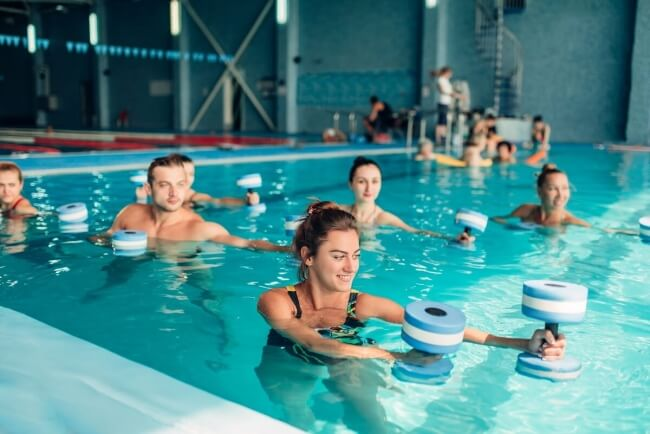 Group of people doing water therapy in indoor pool