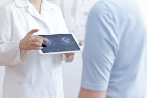 Doctor with tablet showing patient cat scan images of lumbar spine.