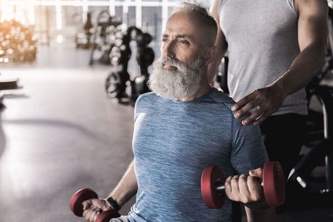 Older man training his biceps in gym with instructor