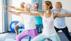 Group of elderly and young men and women doing yoga