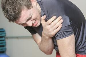 A man in pain grabbing his shoulder