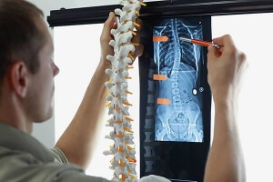 Professional with model of spine watching image of chest at x-ray film viewer.