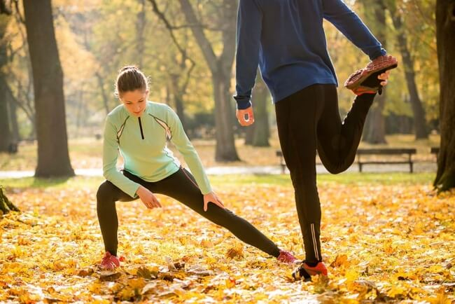 Couple stretching before run in park in the fall