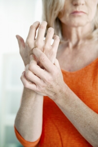 older caucasian woman holding right her sore arthritic wrist