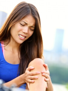 woman holding her left knee in agony