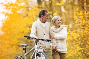 older couple walking together past autumn trees with his mountain bike along side of him