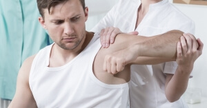 Man having shoulder examined by doctor