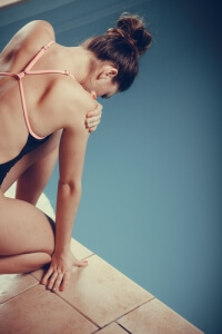 female swimmer kneels by edge of swimming pool holding her sore right shoulder