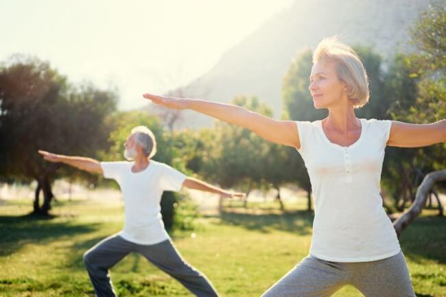Senior couple doing yoga outdoors